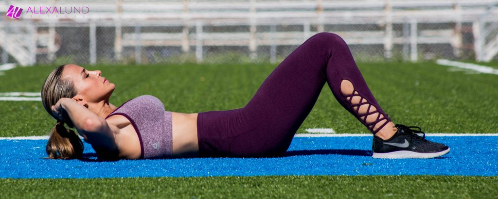 Alexa Lund Fitness doing abdominal exercises on a football field! Purple Outfit and Nike Black Tennis Shoes