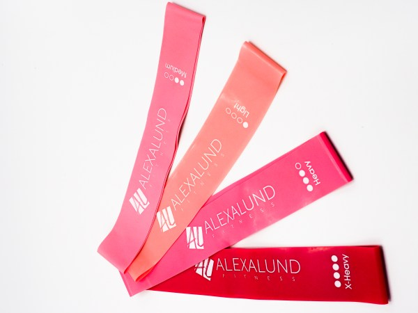 Alexa Lund Fitness Loop Resistance Bands - Set of 4 from Red to coral - Logo in White - Red is extra heavy, pink is heavy, light pink is medium and coral is light