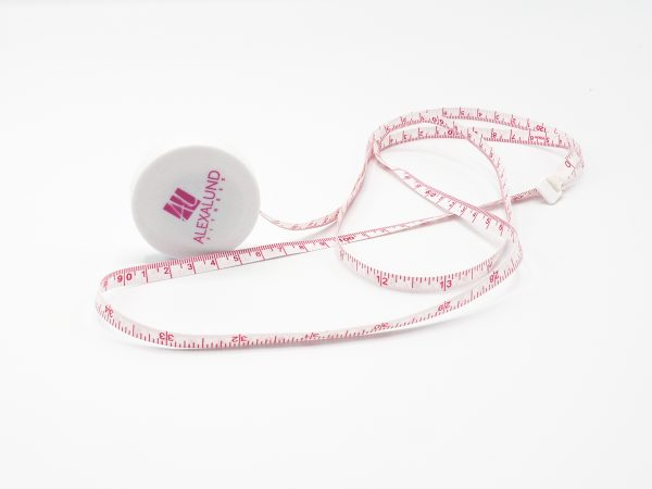 Alexa Lund Fitness Small, White, round Measuring Tape with pink Logo on one side. White tape with pink measurements and numbers